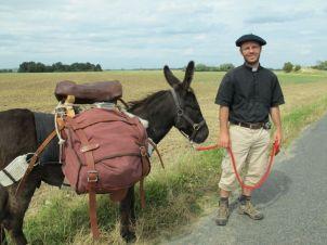 prêtre avec col et un âne en pélérinage